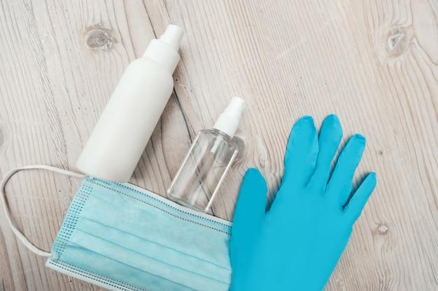 Закройте вверх. защитная маска, перчатки и бактерицидный спрей на столе. фото с копировальным пространством