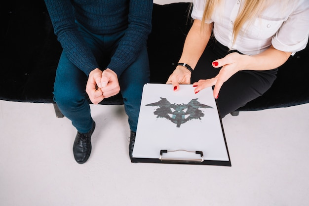 Close-up of a psychologist showing rorschach inkblot on clipboard to patient