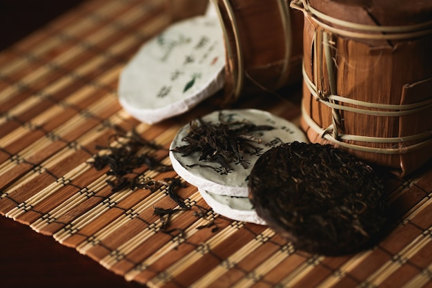 Close up of puer tea with golden toad on a bamboo mat. black background.