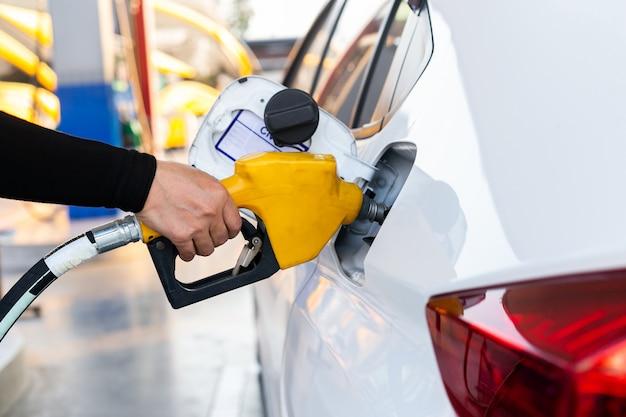 ガソリンスタンドで車のタンクにガソリン燃料ノズルをポンピングをクローズアップ。
