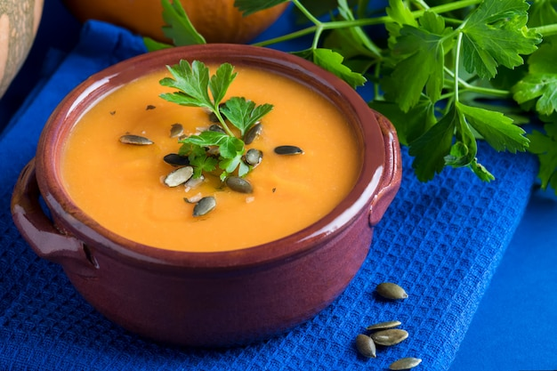 Close up of pumpkin vegan soup in a clay bowl served with parsley, olive oil and pumpkin seeds on the blue background