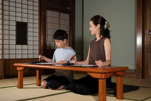 Primo piano sugli alunni che fanno calligrafia giapponese, chiamata shodo