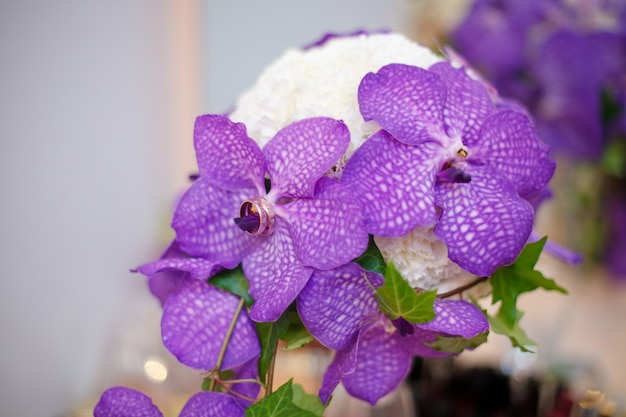 Close up of purple orchid wedding bouquet with rings