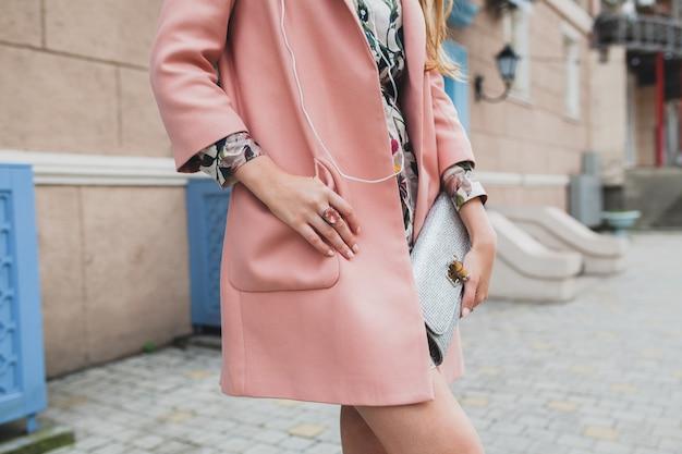 ピンクのコートで街を歩いて魅力的なスタイリッシュな女性の財布を閉じる