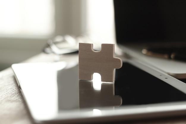 Закройте вверх. кусок головоломки на размытом фоне рабочего стола.