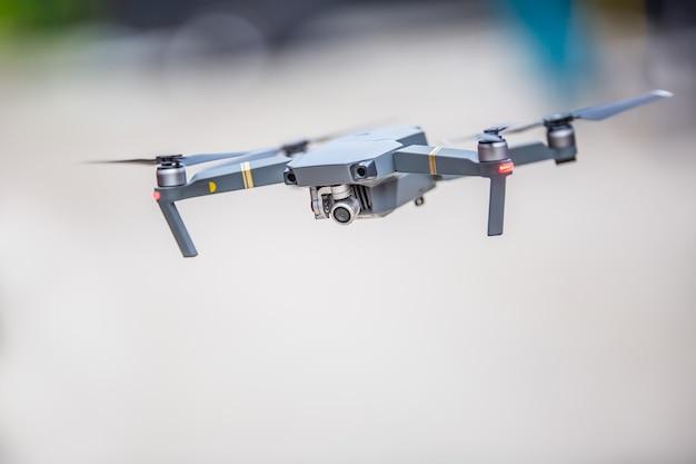 公園を飛んでいるカメラとクローズアップクワッドコプタードローン。