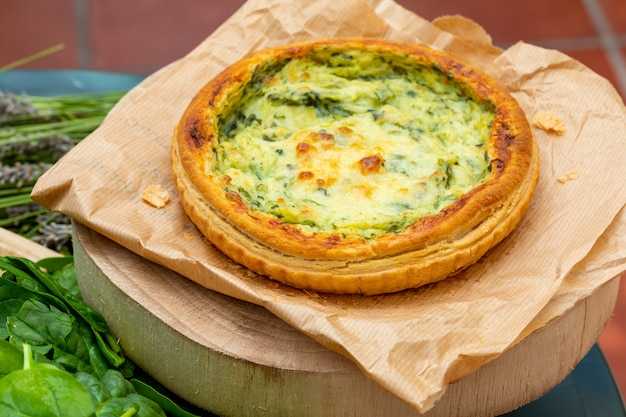Close-up of quiche with fresh vegetables.