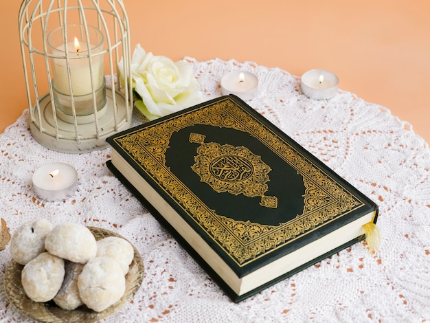 Close  up quran on table  with pastries