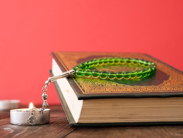 Close up of quran on table with prayer beads