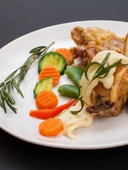Крупным планом кроличьи ножки, запеченные в белом вине с соусом бешамель на керамической тарелке с овощами и розмарином на черном фоне. диетическое мясо кролика, приготовленное в духовке.