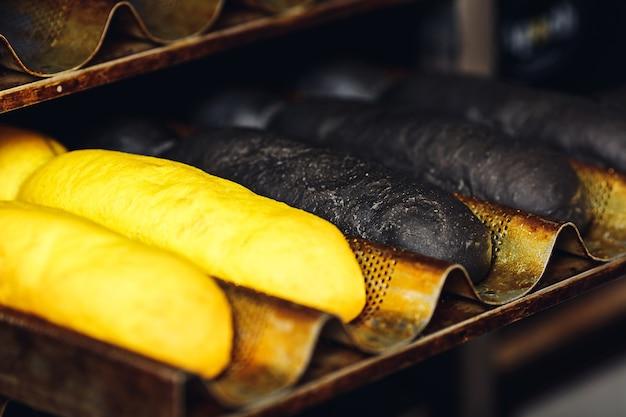 ホットドッグ用の黄色と黒のパンが付いたクローズアップラック。