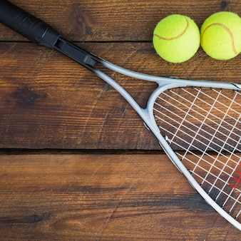 Close-up of racket with two tennis balls on wooden table