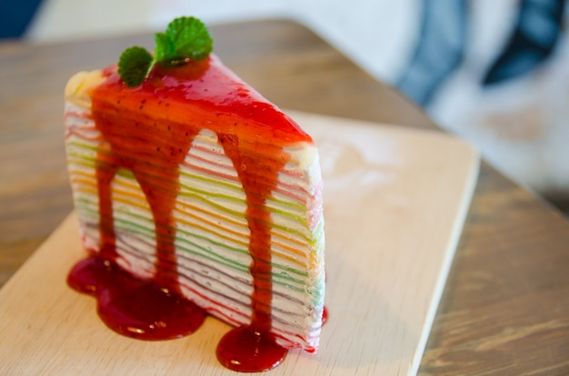 Close up of rainbow crepe cake on wooden plate