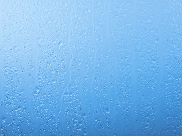 빗방울을 닫고 비오는 날 회색과 푸른 하늘 배경 위에 유리 창 표면에 물이 흐릅니다.