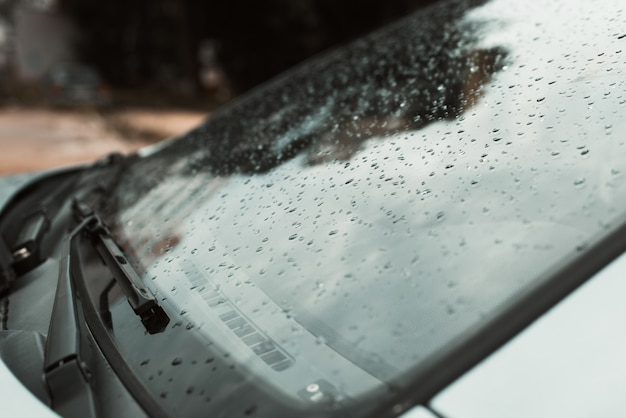 Close-up of raindrops on the windshield of a car in cloudy weather after rain outdoors. side view, selective focus.