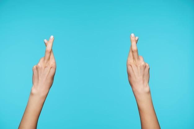 Primo piano di mani alzate dita incrociate mentre si fa il segno del desiderio