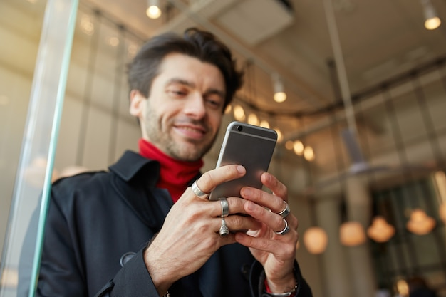 Close-up of raised man's hands with rings keeping mobile phone while posing over city cafe background, texting message to friends and smiling slightly while looking positively on screen