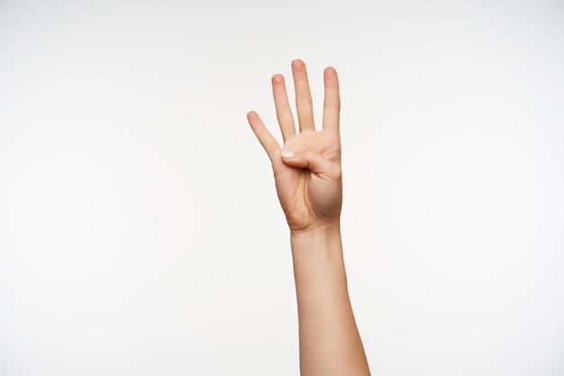 Primo piano sulla mano sollevata della giovane signora graziosa che mostra quattro dita