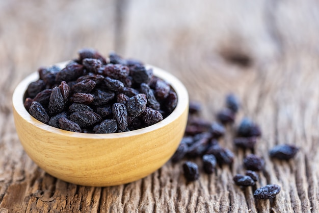 Close up raisins in bowl on wooden table background