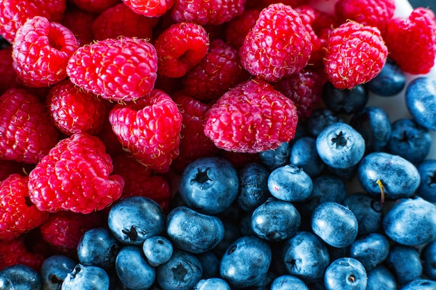 A close-up of raspberries and black blueberry split the frame. summer vitamins