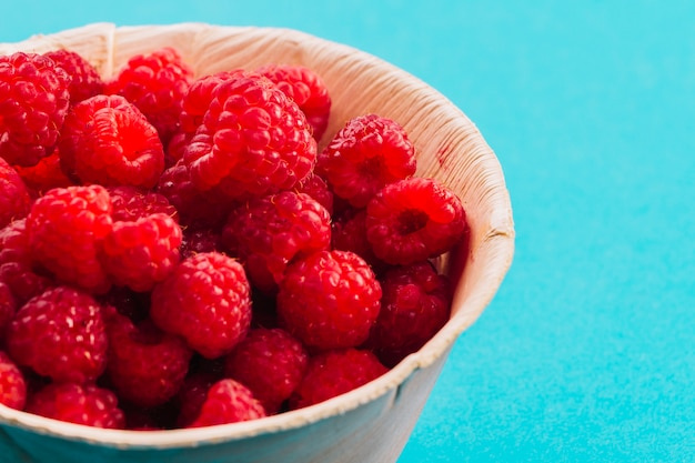 Close-up of raspberries in the bowl on the turquoise backdrop