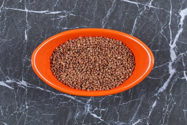 Primo piano grano saraceno crudo. ciotola arancione piena di grano saraceno.