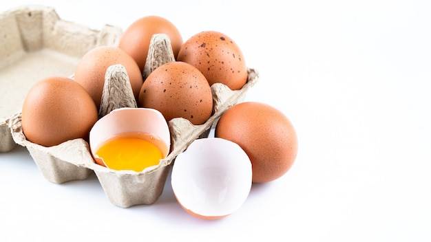Close up of raw chicken eggs in egg box and shell isolated