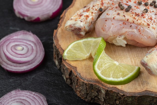 Close up raw chicken legs on wooden board.