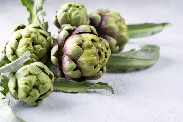 Close-up of raw fresh artichoke on grey stone background.  space for text