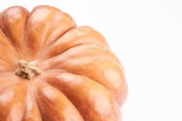 白い食べ物の背景に分離された生のオレンジ色のカボチャのクローズアップ