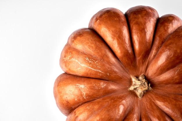 白い食べ物の背景に分離されたクローズアップ生オレンジカボチャ