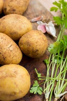 Крупный план сырого картофеля на деревянной доске