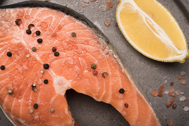 Close-up raw salmon steak and pepper with lemon on tray