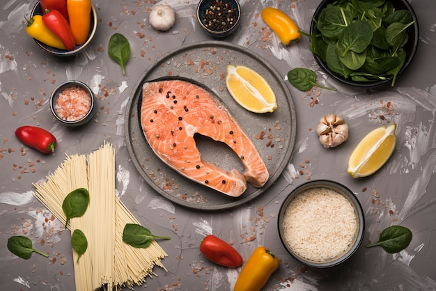 Close-up raw salmon steak on tray with ingredients