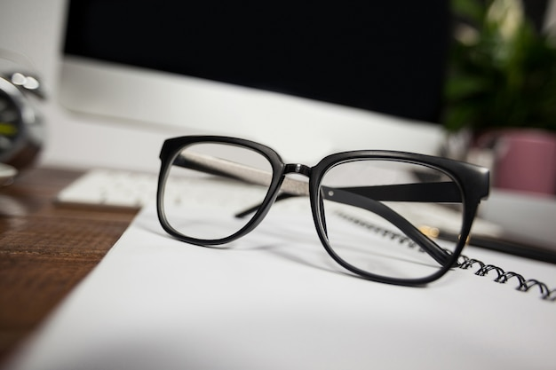 Close- up of reading glasses on office desk