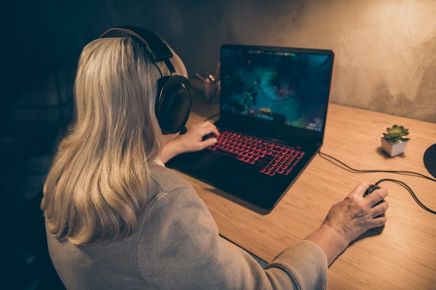 Close-up rear back behind view of her she nice addicted focused concentrated gray-haired blonde grandma mother playing vr game spending free time at industrial loft modern concrete style interior