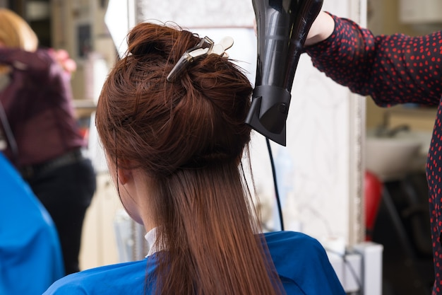 Close up rear view of brunette woman having wet hair dried with hand held blow dryer by stylist in salon