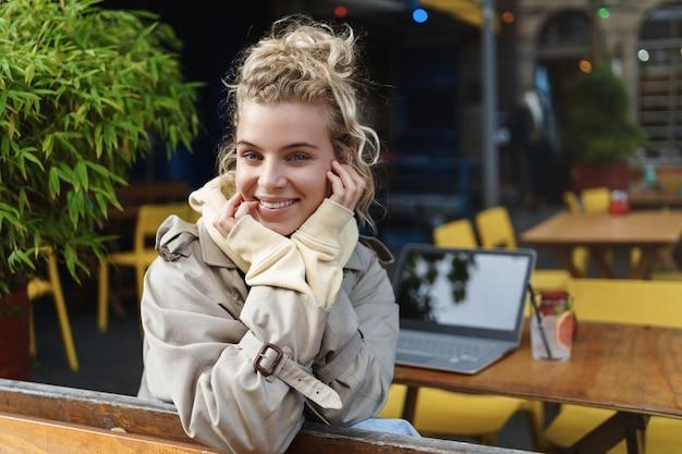 Крупным планом вид сзади красивая блондинка превращается в камеру, сидя за журнальным столиком с портативным компьютером и коктейлем.