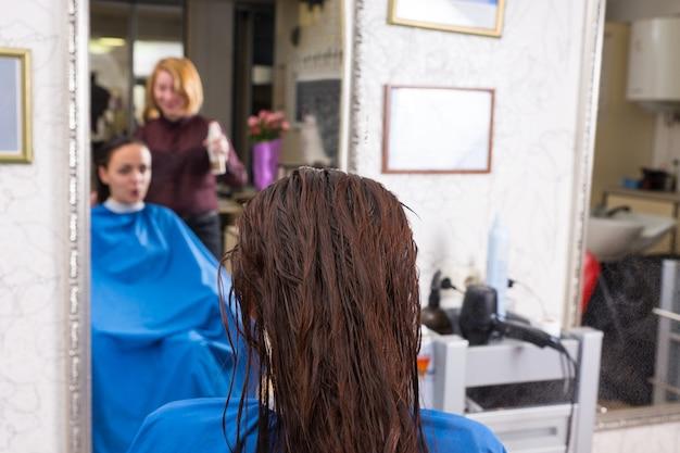 スタイリストとバックミラーのミラーの女性の反射でサロンの椅子に座っている濡れた髪のブルネットの女性の背面図をクローズアップ