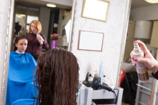 背景にぼやけた鏡の反射でサロンの椅子に座っているブルネットの女性クライアントの濡れた髪に製品をスプレーするスタイリストの背面図を閉じる