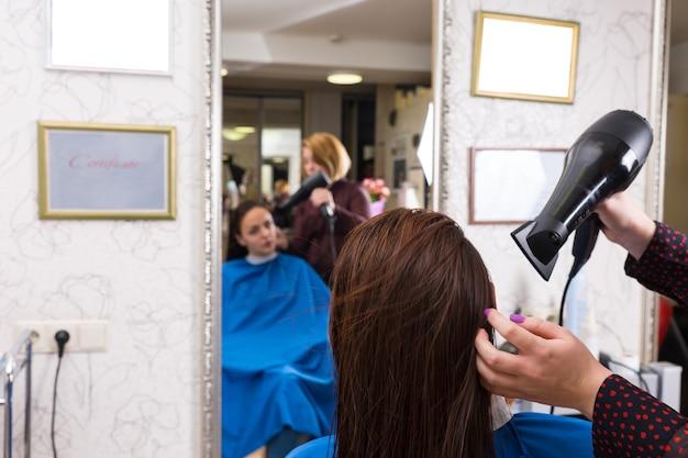 バックミラーのぼやけた反射でサロンの椅子に座っているブルネットの女性の濡れた髪を乾かすためにブロードライヤーを使用してスタイリストの背面図をクローズアップ