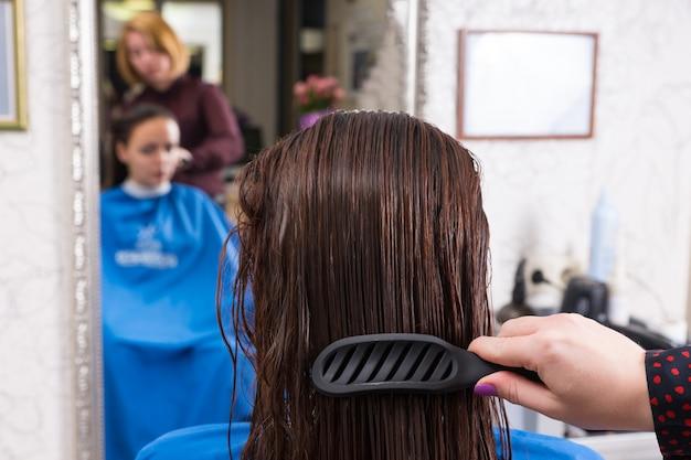 バックミラーのぼやけた反射でサロンの椅子に座っているブルネットの女性の濡れた髪をとかすためにブラシを使用してスタイリストの背面図を閉じる