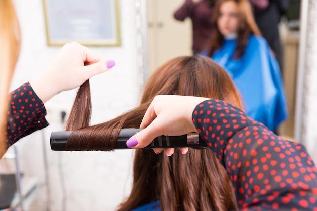 バックグラウンドでミラーの焦点が合っていない反射でサロンの椅子に座っている女性のブルネットのクライアントの髪にフラットアイロンを使用してスタイリストの背面図を閉じる