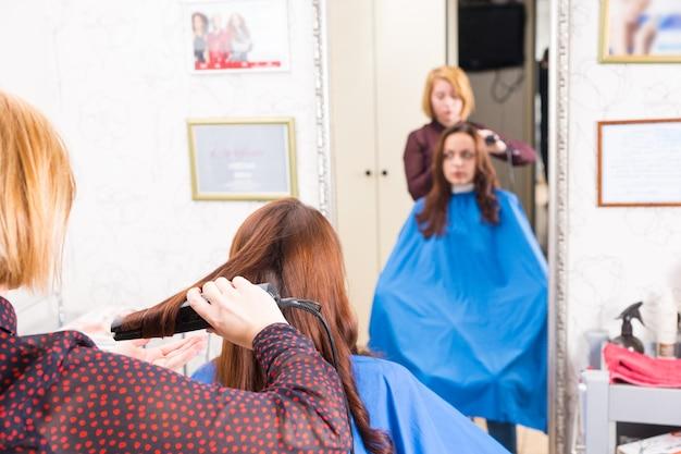 背景の大きな鏡でぼやけた反射とサロンで女性ブルネットクライアントの長い髪にフラットアイロンを使用してスタイリストの背面図をクローズアップ