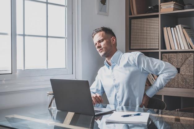 座りがちな生活やホームオフィスでの間違った姿勢での長時間のコンピューターの過労による突然の痛みに苦しんでいる、不快感を感じて腰に触れている若い男性を強調した背面図を閉じます。