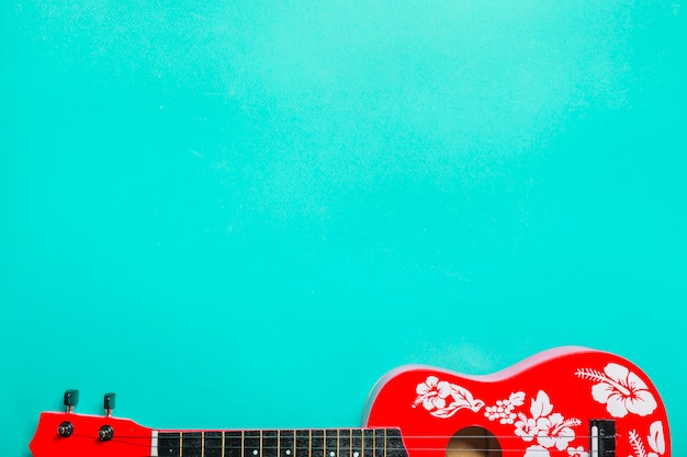 Close-up of red acoustic classic guitar on turquoise background