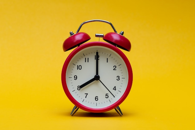 Close up red alarm clock on yellow background