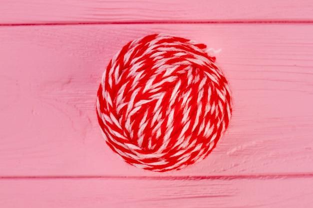 모직 스레드의 빨간 공을 닫습니다. 분홍색 나무 배경에 뜨개질 원사의 빨간 공.