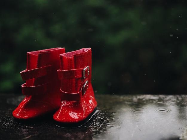 Закройте вверх по красной резине ботинок на влажном поле.
