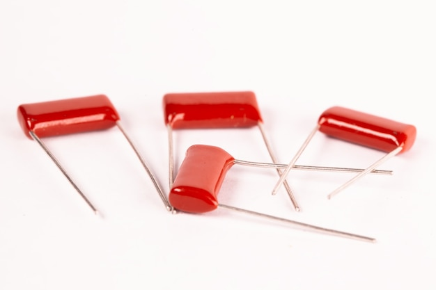 Close-up red capacitors lie on a white table during the production of office equipment and powerful computers for mining and video games.